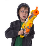 Young boy with hood aiming his toy gun Royalty Free Stock Photos