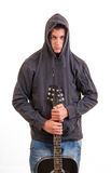Young boy in hoodie standing and holding his guitar Royalty Free Stock Photos
