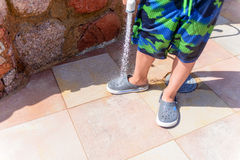Young boy hosing the sand off himself and his shoe Stock Photos