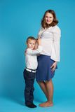 Young boy hug pregnant mother Stock Images