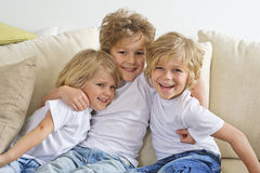Young boy hugging his brothers. Three brothers hugging and playing on the sofa stock photo