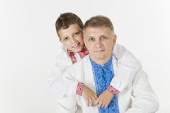 Young boy is hugging his father lovingly. Boy is hugging his father from behind isolated on white Royalty Free Stock Photo