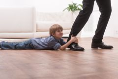 Young boy hugging his father's leg. Cute boy holding man and lying on floor Royalty Free Stock Photo