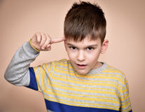 Young boy with the index finger on his head Royalty Free Stock Images