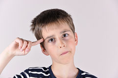 Young boy with the index finger on his head Royalty Free Stock Photo