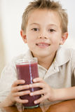 Young boy indoors drinking juice Royalty Free Stock Photo