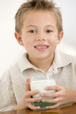 Young boy indoors drinking milk Stock Image
