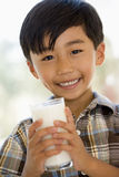 Young boy indoors drinking milk smiling Stock Photos