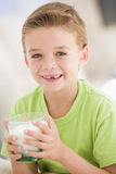 Young boy indoors drinking milk smiling. At camera Royalty Free Stock Photography