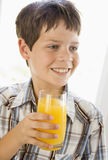 Young boy indoors drinking orange juice smiling Royalty Free Stock Photography