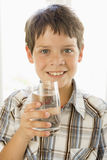 Young boy indoors drinking water smiling stock photography