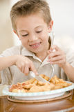 Young boy indoors eating fish and chips Stock Image