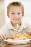 Young boy indoors eating fish and chips Royalty Free Stock Photos