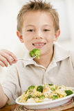 Young boy indoors eating pasta with brocolli. Smiling Royalty Free Stock Photography