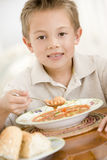 Young boy indoors eating soup. Looking at camera Royalty Free Stock Photography
