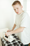 Young Boy Ironing Shirt and Looking Grumpy Stock Images