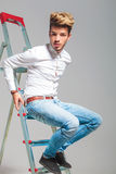 Young boy in jeans and white shirt climb on a ladder. In studio background royalty free stock image
