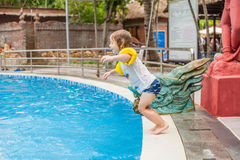 Young boy jump into the water of swimming pool Stock Photo