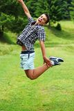 Young boy jumping. Against green landscape Royalty Free Stock Images