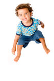 Young Boy Jumping. A cute young boy jumping in the air on white background stock photo