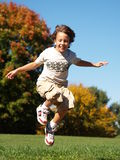 Young boy jumping in air. Young boy jumping in the air on a clear autumn day.  There are trees with colored leaves and blue sky in the background Stock Photos