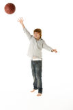 Young Boy Jumping With Basketball. In Studio Stock Photography
