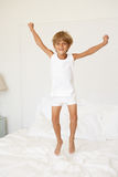 Young Boy Jumping On Bed. Having Fun Stock Images