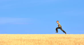Young boy jumping on field. Under blue sky Stock Image