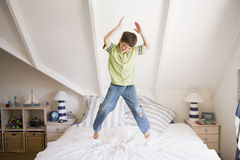 Young Boy Jumping On His Bed. Smiling Stock Images