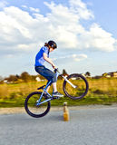 Young boy jumping with his dirk bike over a barrier at the stree. T Stock Images
