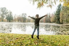 Young boy jumping for joy. With outstretched arms as he celebrates the tranquility of an autumn landscape with lake and fallen leaves on the grass, with lateral Royalty Free Stock Photos