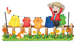 A young boy jumping near the hanging clothes Stock Photo