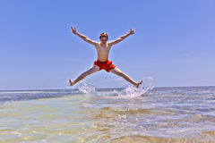 Young boy jumping out of the water. At the tropical beach Royalty Free Stock Photography