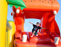 Young boy jumping on a plastic jumping castle. Young boy jumping barefoot on a plastic jumping castle with his arms in the air as he enjoys a summer day at a Royalty Free Stock Images