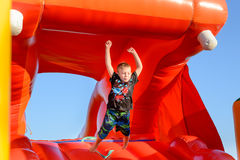 Young boy jumping on a plastic jumping castle. Young boy jumping barefoot on a plastic jumping castle with his arms in the air as he enjoys a summer day at a Royalty Free Stock Photos