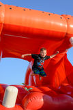 Young boy jumping on a plastic jumping castle. Young boy jumping barefoot on a plastic jumping castle with his arms in the air as he enjoys a summer day at a Stock Photography