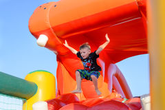 Young boy jumping on a plastic jumping castle. Young boy jumping barefoot on a plastic jumping castle with his arms in the air as he enjoys a summer day at a Royalty Free Stock Photo