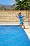 Young boy jumping into pool. Young boy jumping into swimming pool on sunny vacation or holiday Stock Photography