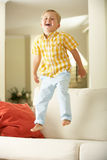 Young Boy Jumping On Sofa At Home. Smiling At Camera Royalty Free Stock Images