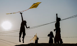 A young boy jumping up for the flying kite Royalty Free Stock Images