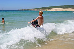Young boy jumping into wave on a sunny beach. In Spain on vacation Royalty Free Stock Photography