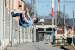 A young boy jumps somersault on the street. A young boy jumps somersault in the street Royalty Free Stock Photo