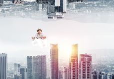 Young boy keeping mind conscious. Young boy keeping eyes closed and looking concentrated while meditating on cloud in the air between two urban worlds Royalty Free Stock Photos