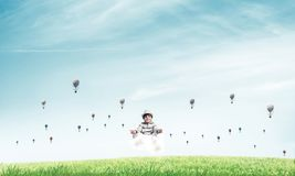 Young boy keeping mind conscious. Young little boy keeping eyes closed and looking concentrated while meditating on cloud among flying aerostats with bright and Stock Photography