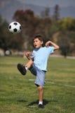 Young boy kicking a soccer ball. A young boy kicks a soccer ball in a park setting Stock Photo