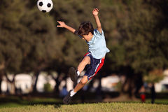 Young boy kicking a soccer ball in the park Royalty Free Stock Image