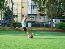 Young boy kicks the ball to goal Stock Photos
