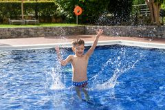 Boy plaiyng in swimming pool. Young boy kid child splashing in swimming pool having fun leisure activity open arms royalty free stock photography