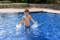 Boy plaiyng in swimming pool. Young boy kid child splashing in swimming pool having fun leisure activity open arms stock photo