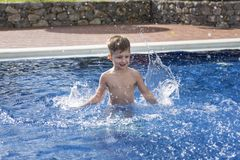 Boy plaiyng in swimming pool royalty free stock photo